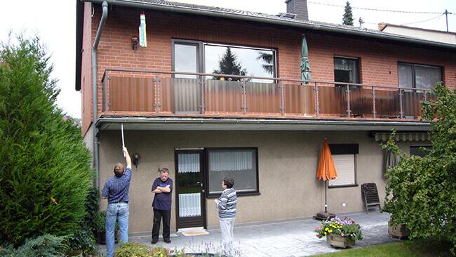 VOSS Mitarbeiter nimmt Maß für einen Wintergarten im ersten Obergeschoss eines Wohnhauses